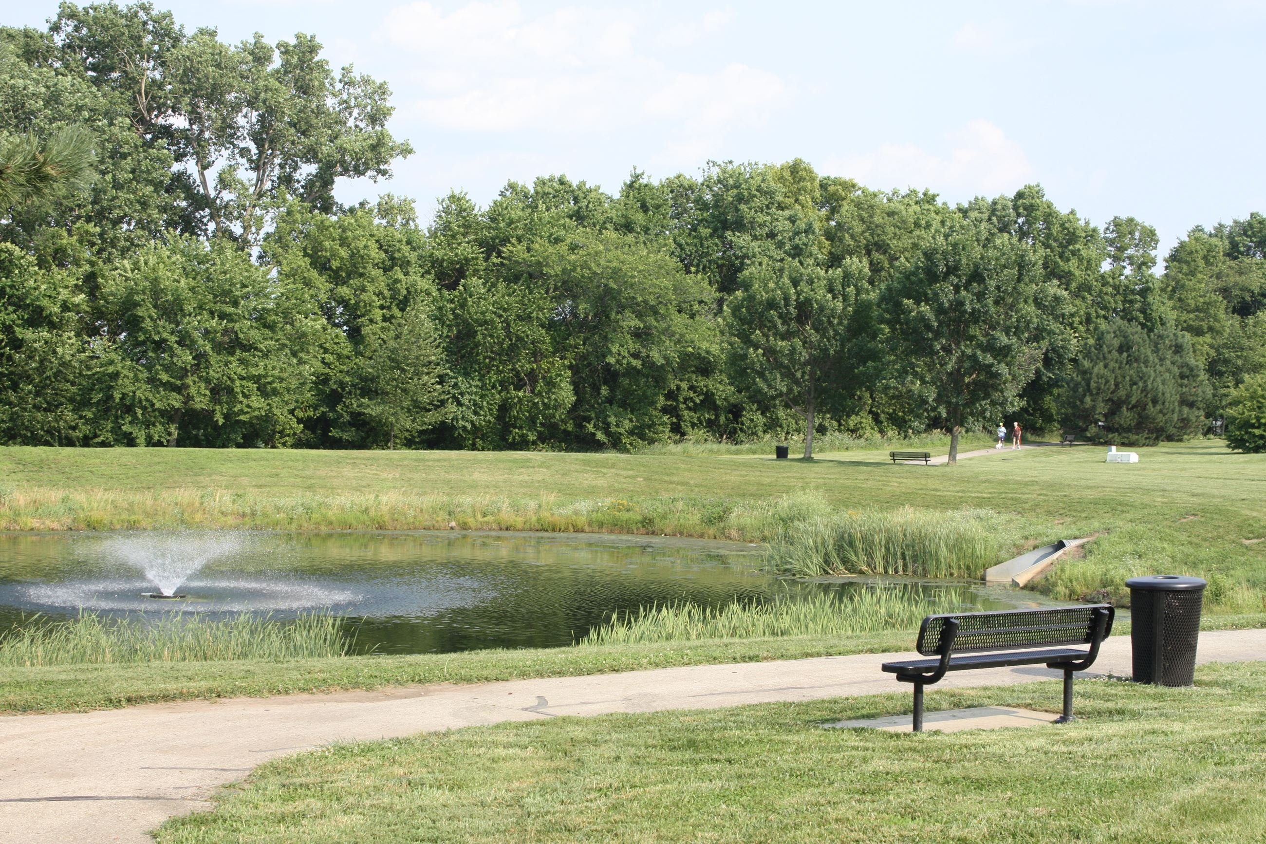 An outdoor image showing a pond and fountain at Blackhawk Park with trees lining the background.