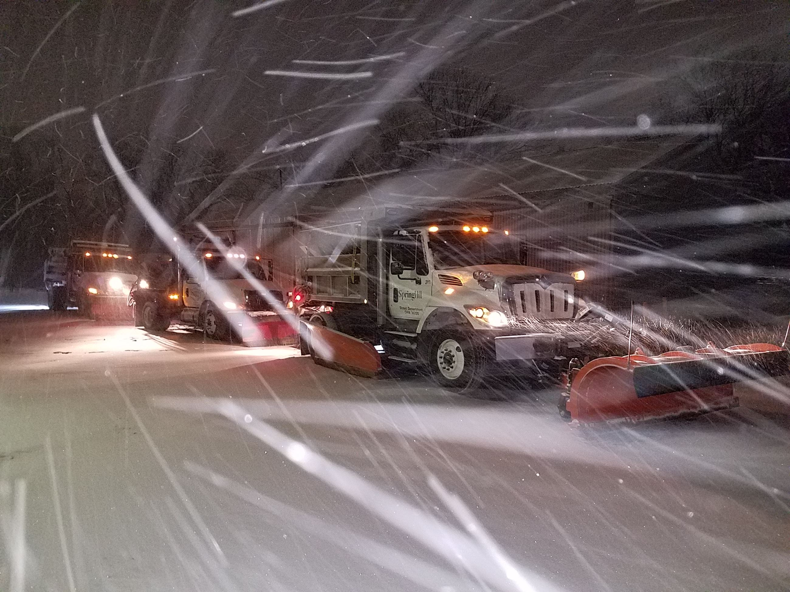 Snow plow trucks stacked up in snowy weather