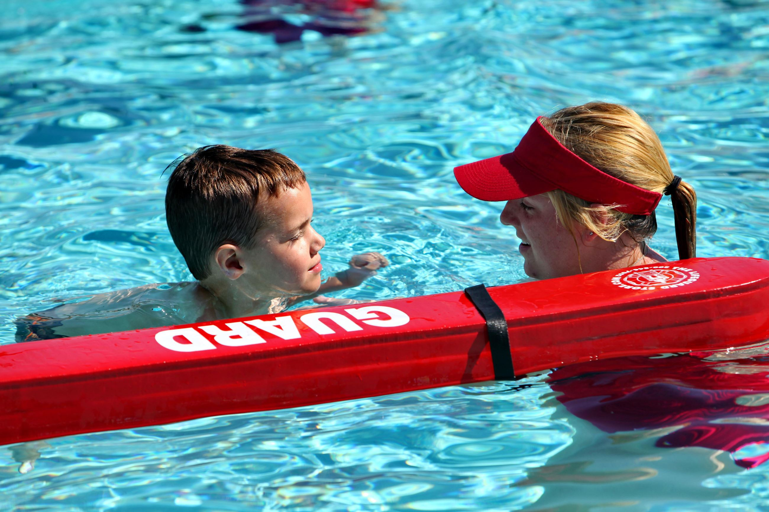 Swim instructor helping child learn to swim
