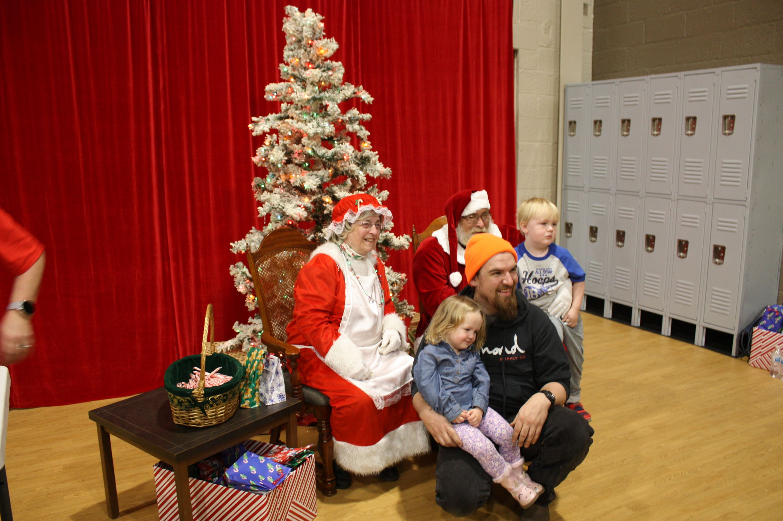 Family poses for photo with Santa and Mrs. Claus